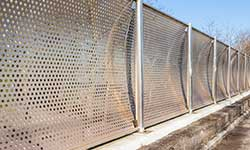 perforated metal infill panels at train station